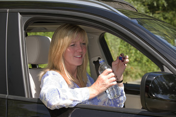 Woman driver seated in car holding bottled water