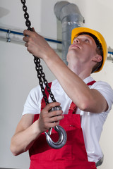 Man preparing crane hook to lifting materials