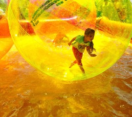 child playing in the pool inside a plastic ball