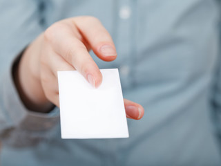 white business card in between fingers