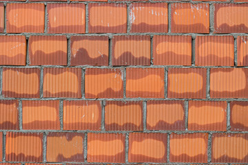 Orange hollow clay block in fresh mortar, wall background
