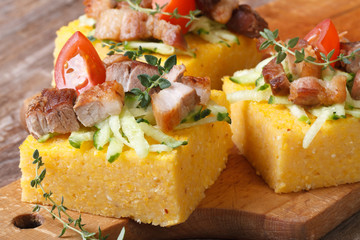 Polenta with bacon, vegetables and thyme on wooden board