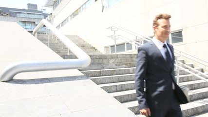Businessman walking down stairs in town