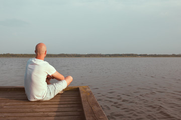 Man sitting in a wooden dock in a lake