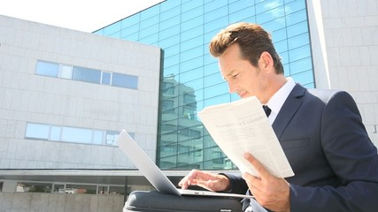 Portrait of businessman sitting outside office building