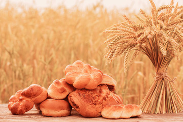 bread and wheat on the wooden table in autumn field