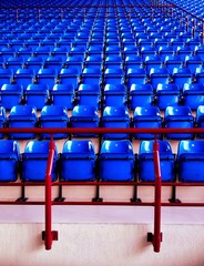 empty blue plastic chairs at the stadium
