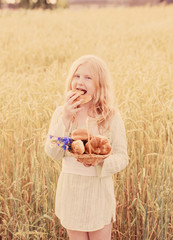 Cute little girl eating bread on wheat field