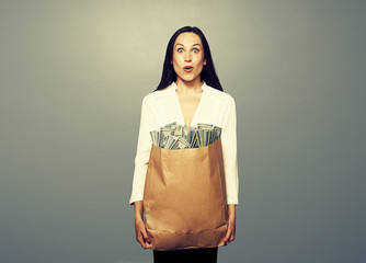 amazed woman holding paper bag with money