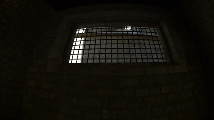 Looking out from medieval dungeon barred window