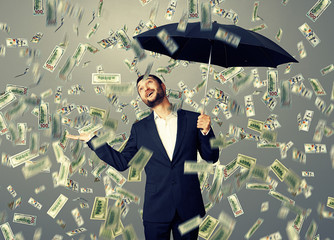 man standing under money rain