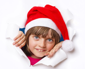 little girl with santa cap looking out of a hole in a paper