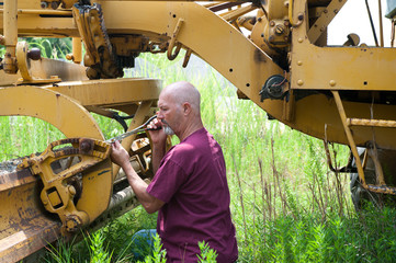 Man using pliers to work on blade of roadgrader