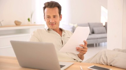 Man at home working on laptop computer