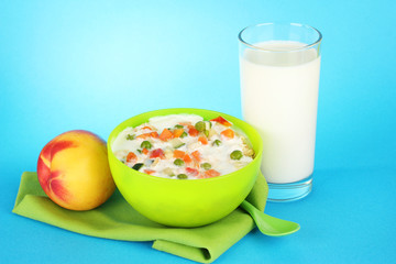 tasty dieting food, fruits and glass of milk, on blue
