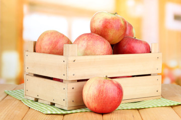 Ripe apples in wooden box, on bright background