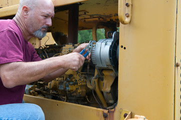 Man using pliars to install new alternator on roadgrader