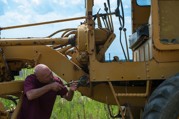 Man using pliers to work on electrical system of bulldozer