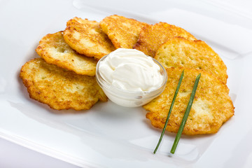 Potato Pancake with sour cream on white