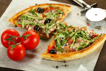 Pizza with arugula on cutting board, on color wooden background