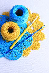 Colorful clews and crochet hooks on light background