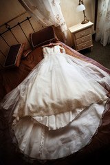 Wedding dress lying on a bed