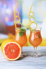 Grapefruit cocktail with cocktail straw on bright background