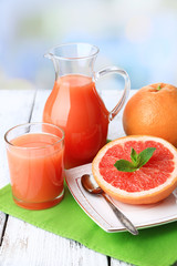 Half of grapefruit, glass jug with fresh juice and spoon