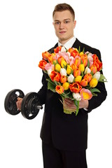 Young man at suit holds dumbbell and big bouquet of tulips