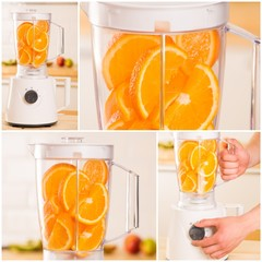 White blender with juicy oranges on a wooden table