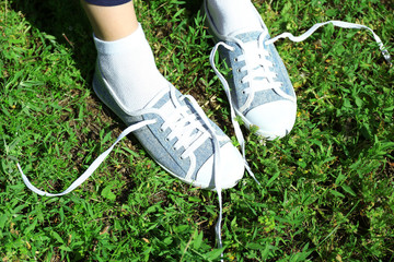 Female legs in sneakers in green grass