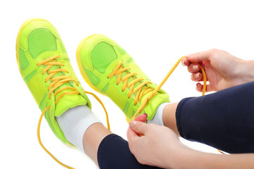 Young woman tying shoelace isolated on white