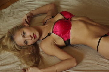 A beautiful young sexy blonde girl lying in the bed