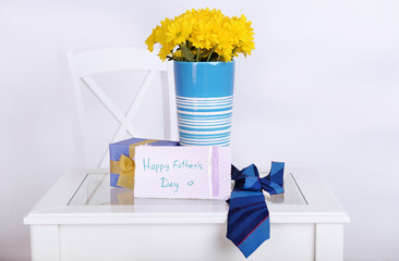 Bouquet of flowers, gift box and tie on Fathers Day in room