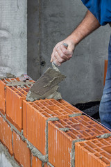 Construction worker using trowel on a hollow clay block wall 3