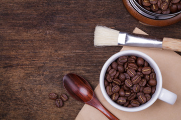 cup of coffee beans on the brown wooden background