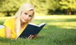 Blonde Girl with Book on Green Grass. Beautiful Woman Outdoor.