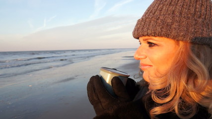 Woman drinking tea at the beach at sunset