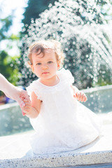 small child on a background of splashing fountain