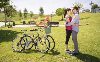 Couple in love embraced beside of bicycles on park