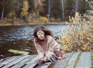Girl in ethnic style on the shore of a lake in autumn