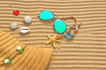 Sunglasses, Straw Hat and  different objects on the beach sand