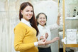 saleswoman helps bride chooses bridal accessories