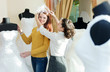 consultant helps girl chooses white bridal outfit