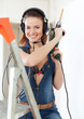 beauty woman in headphones with drill