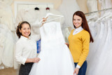 Shop assistant  helps the bride in choosing  dress