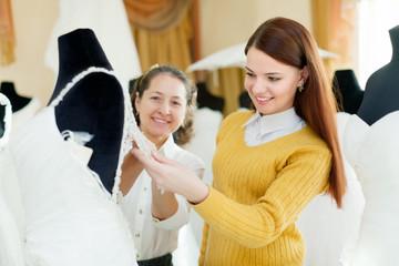 Friendly shop consultan helps the bride