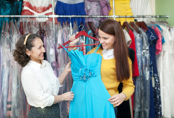 pretty girl chooses evening dress at boutique