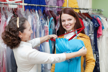 Girl chooses evening dress at clothing store