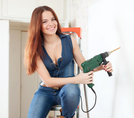 Happy girl in overalls with drill